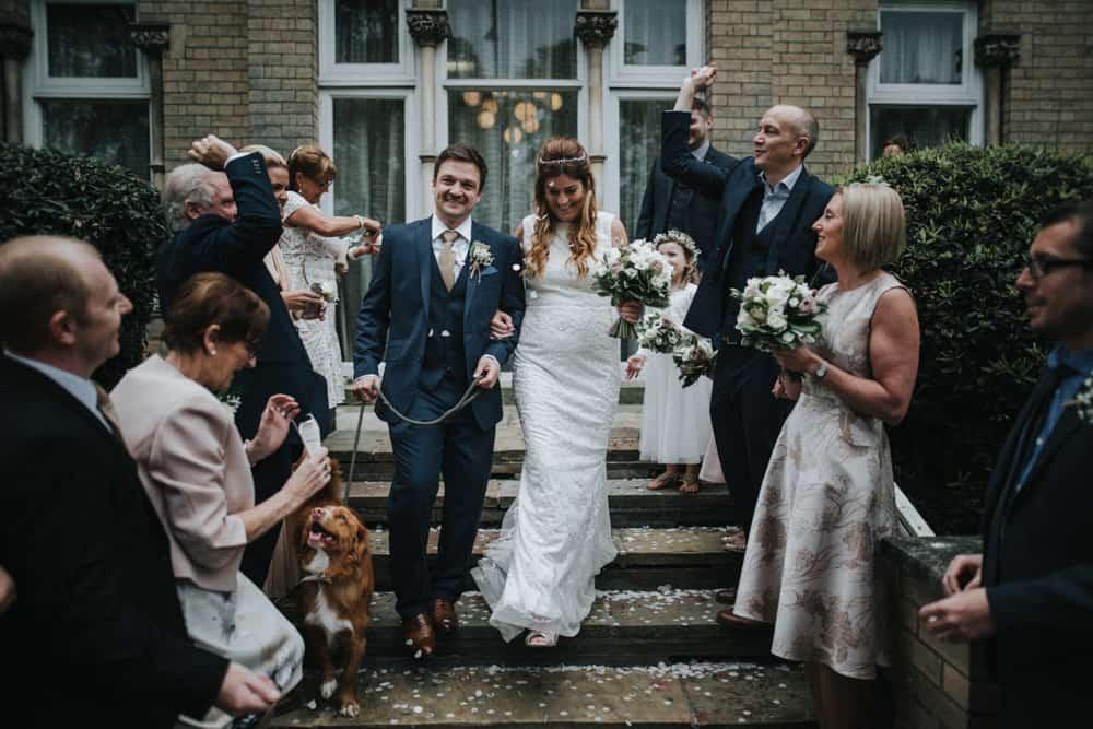 Bride, Groom and their dog walk through a confetti procession