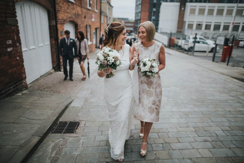 Bride & Bridesmaid laughing as they walk from ceremony in Lincoln