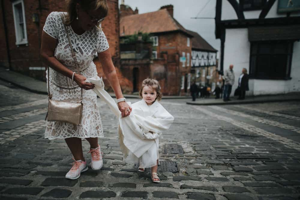 Little flowergirl walking through streets of Lincoln with grandmother wrapped in her Dad's jacket