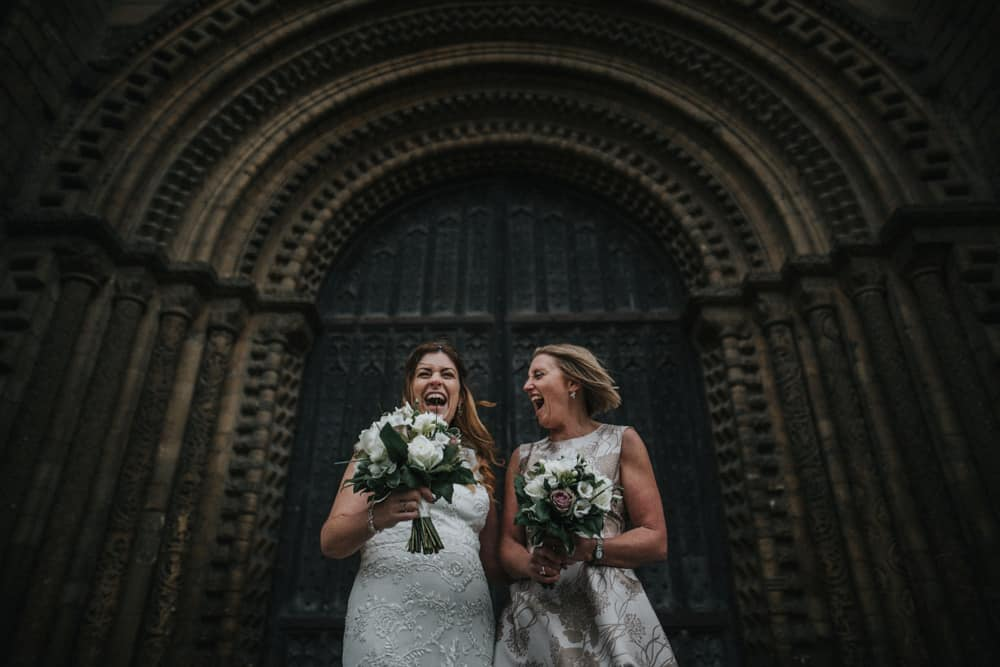 Bride & Bridesmaid laughing on steps of Lincoln Cathedral