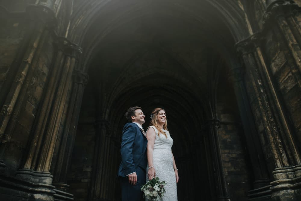 Bride & groom outside arched doors of Lincoln Cathedral