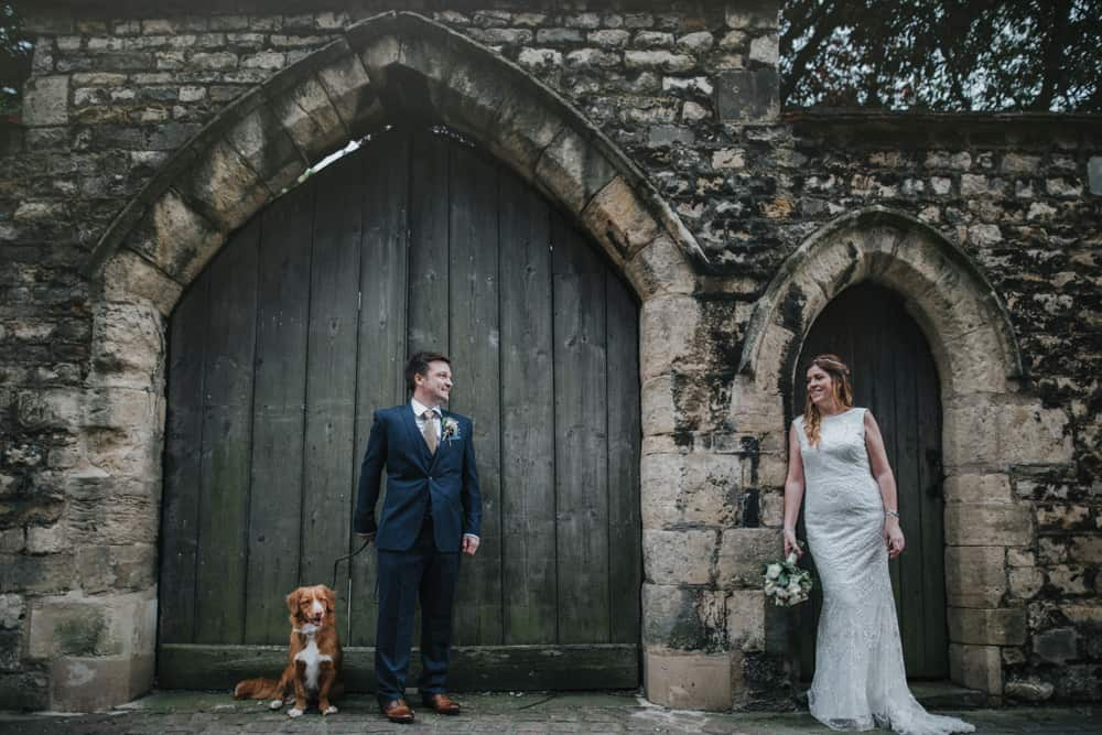 Bride, Groom & their dog outside the doors of Lincoln Cathedral