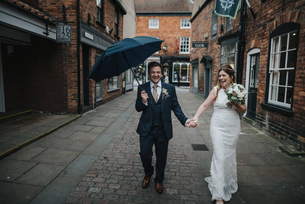 Bride & Groom walking through streets on Lincoln, with the groom holding and umbrella laughing