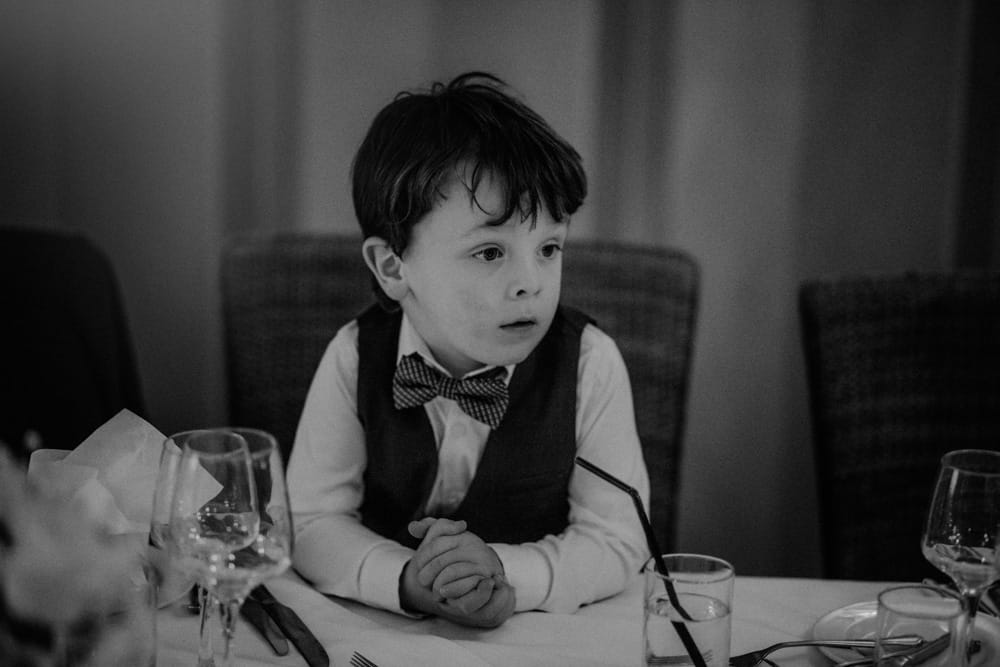 Little boy in bow tie at wedding leaning on table with hands together
