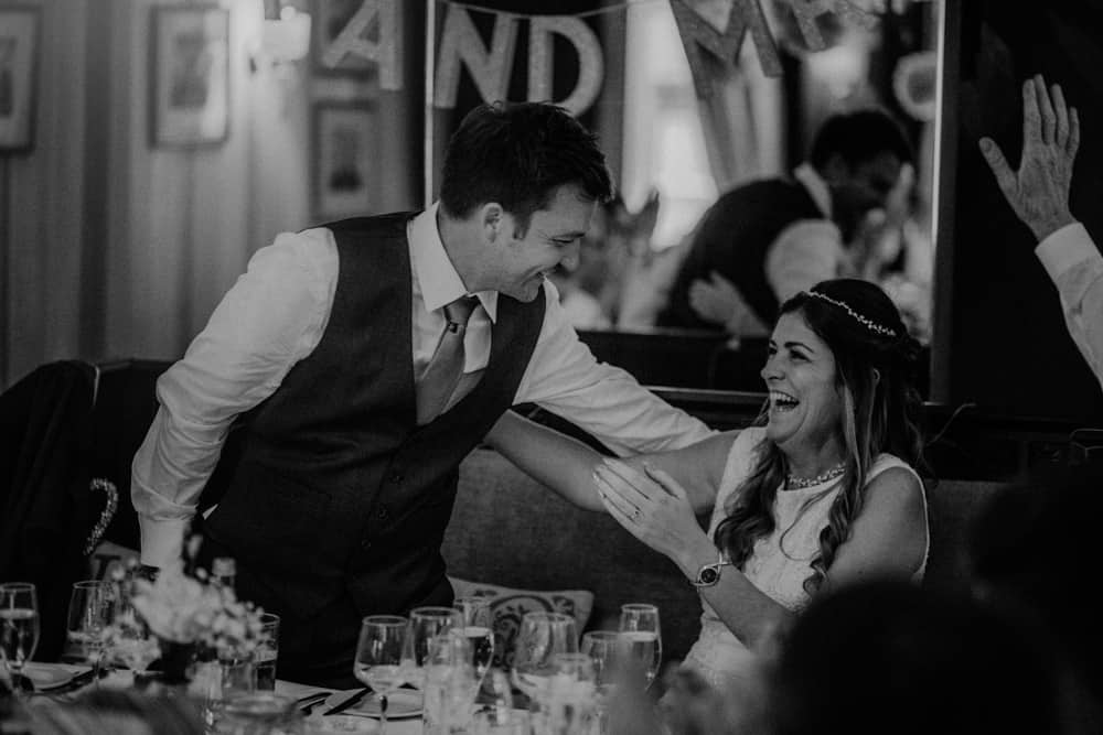 Bride & Groom laughing at small intimate wedding dinner