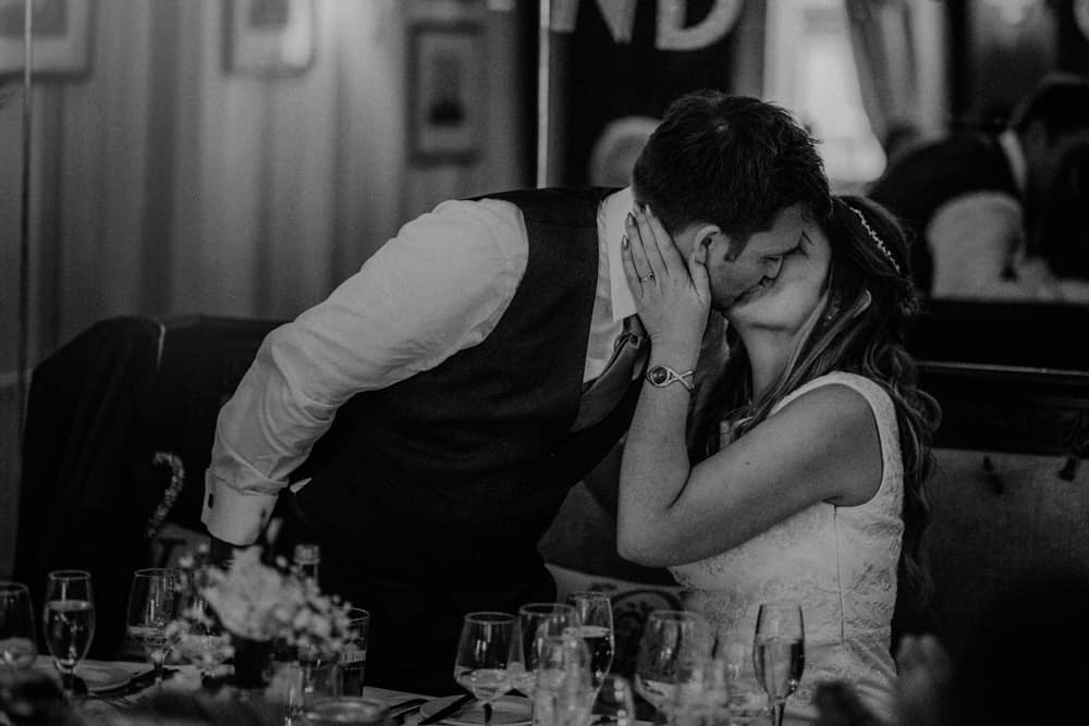 Groom kissing his bride at small intimate wedding dinner