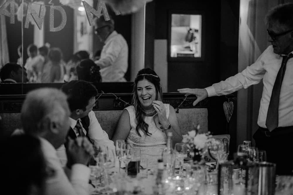 Bride & Groom laughing during father of the bride's speech at small intimate wedding dinner