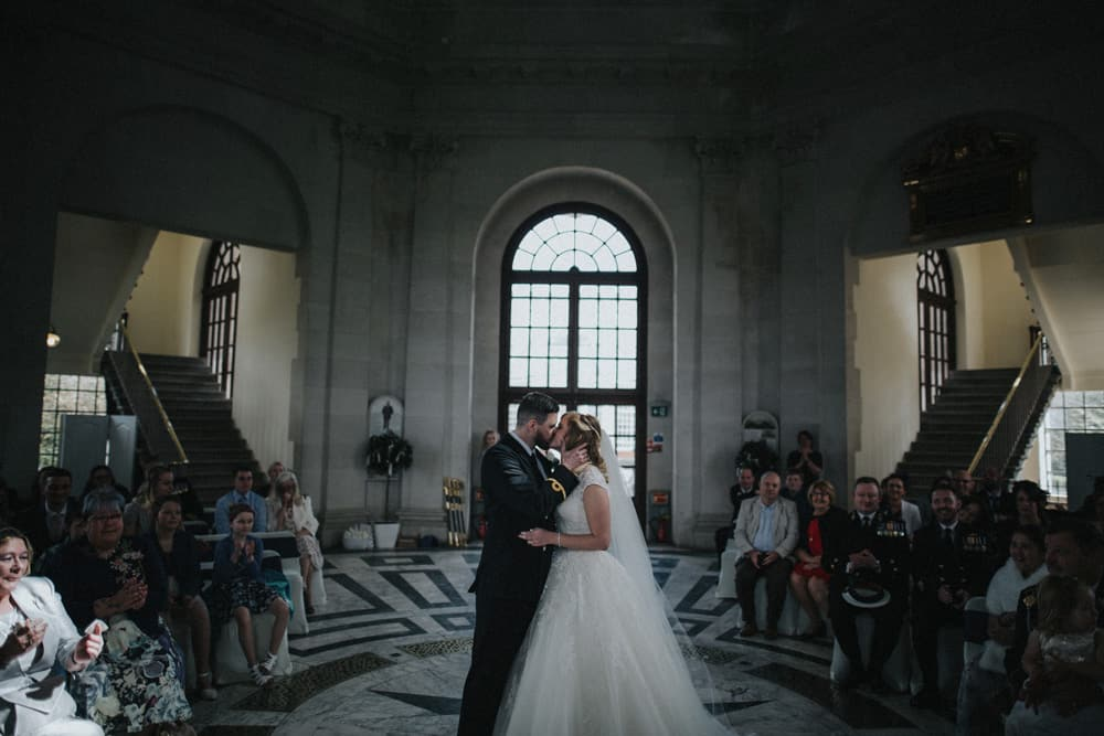 The first kiss of the bride and groom at their wedding at the Ashton Memorial in Lancaster