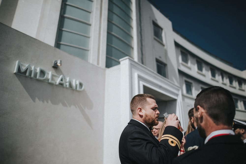 Guests stand outside the Midland Hotel in Morecambe having a drink in the sunshine