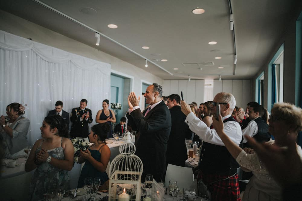 Guests welcome the bride and groom into the wedding breakfast