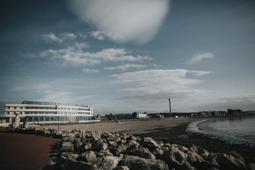 The midland Hotel in Morecambe from the beach with blue skies