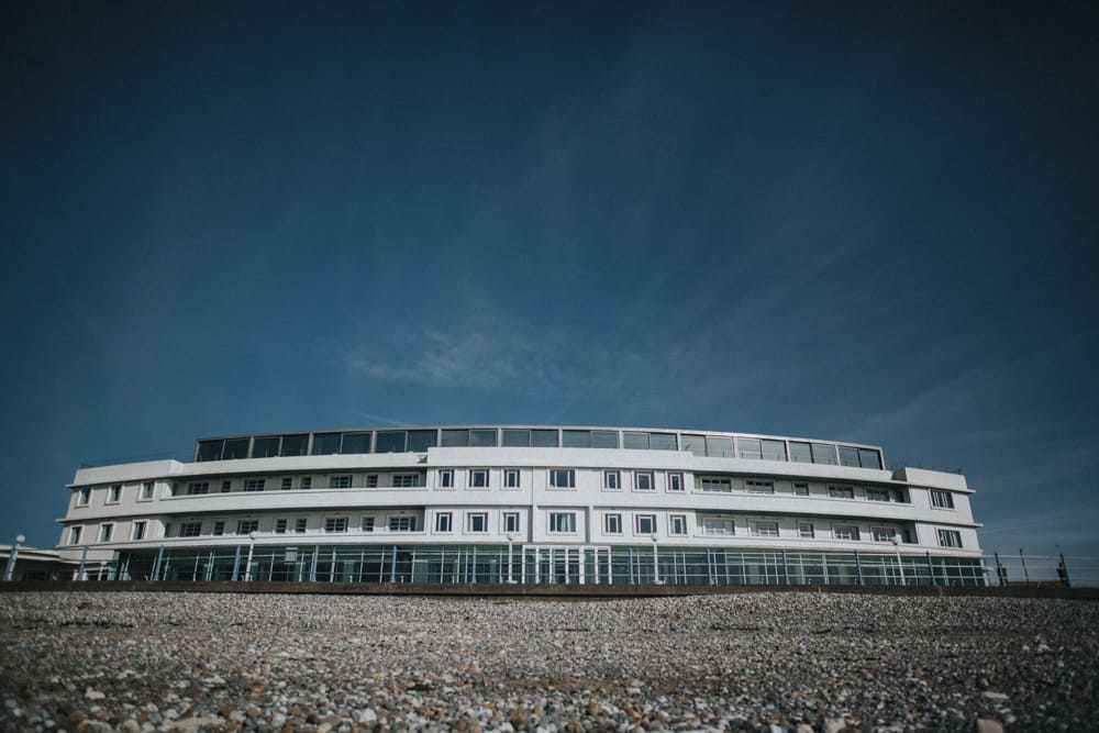 The outside of the Midland Hotel in Morecambe taken from the beach with blue skies