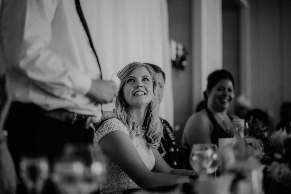 The Bride looks on to her husband laughing at his speech