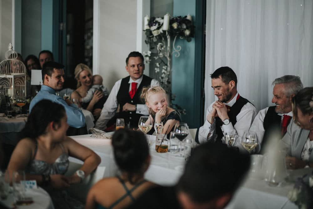 Little bridesmaid laughing as she is mentioned in the wedding speech