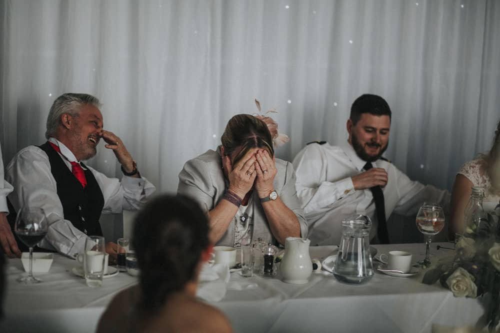 Mother of the groom covers her face laughing