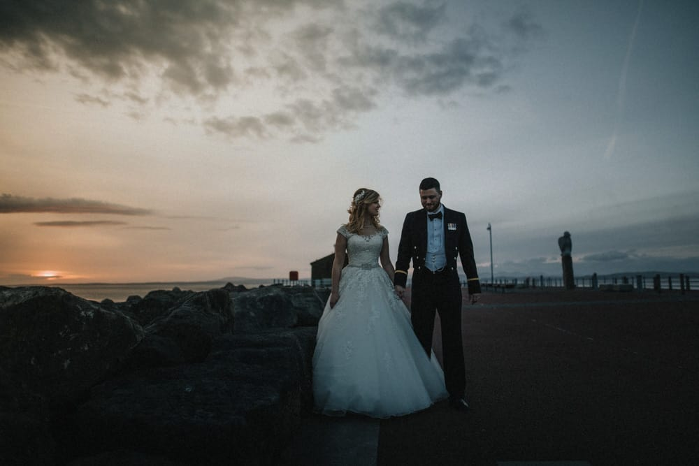 Bride and Groom have their pictures taken at sunset on the pier outside the Midland Hotel in Morecambe