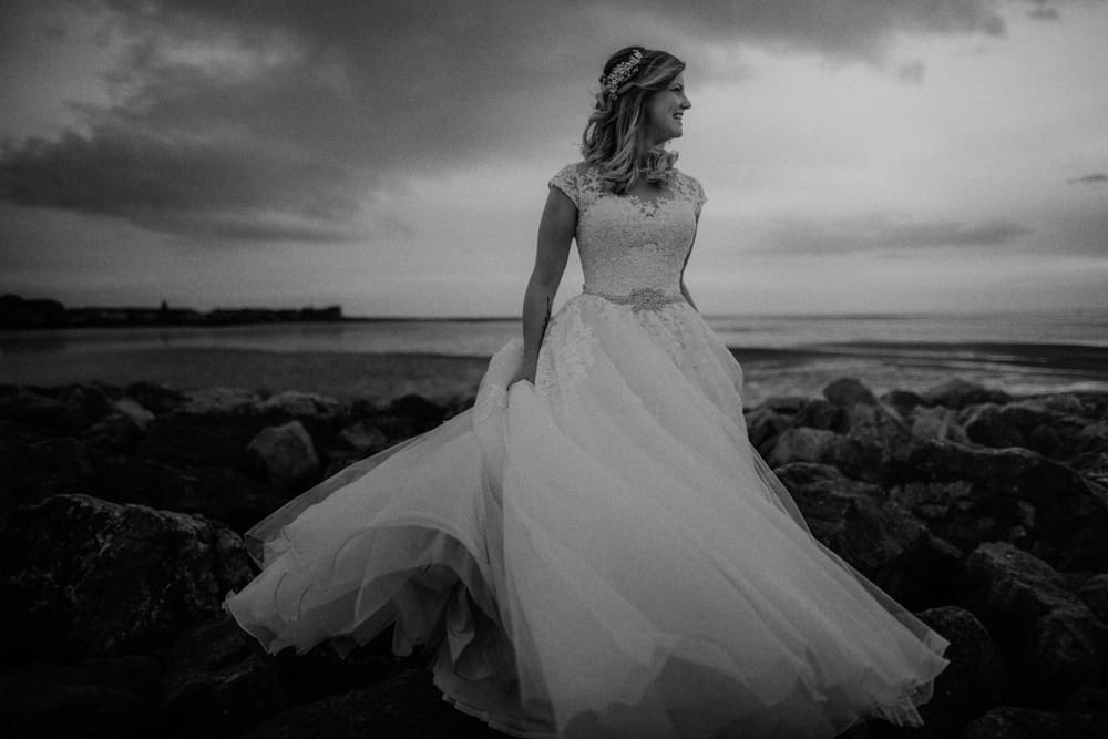 Bride dances at sunset on the pier in Morecambe in her wedding dress
