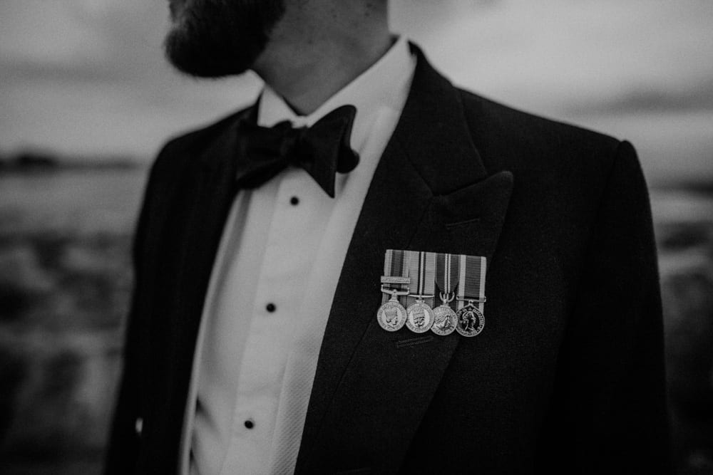 Groom poses his military medals during photo shoot