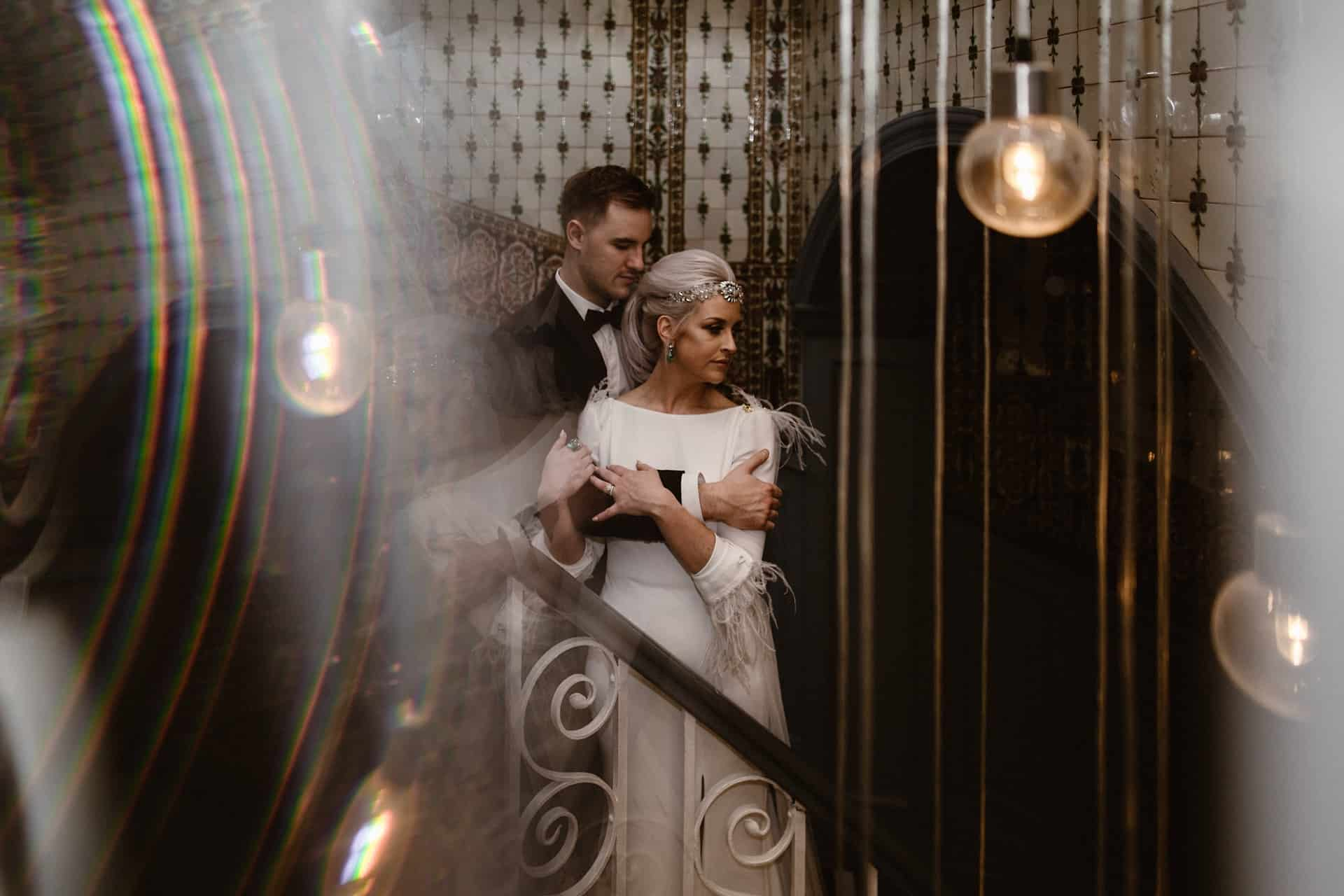 Couple embrace on the staircase at the Midland Hotel Manchester