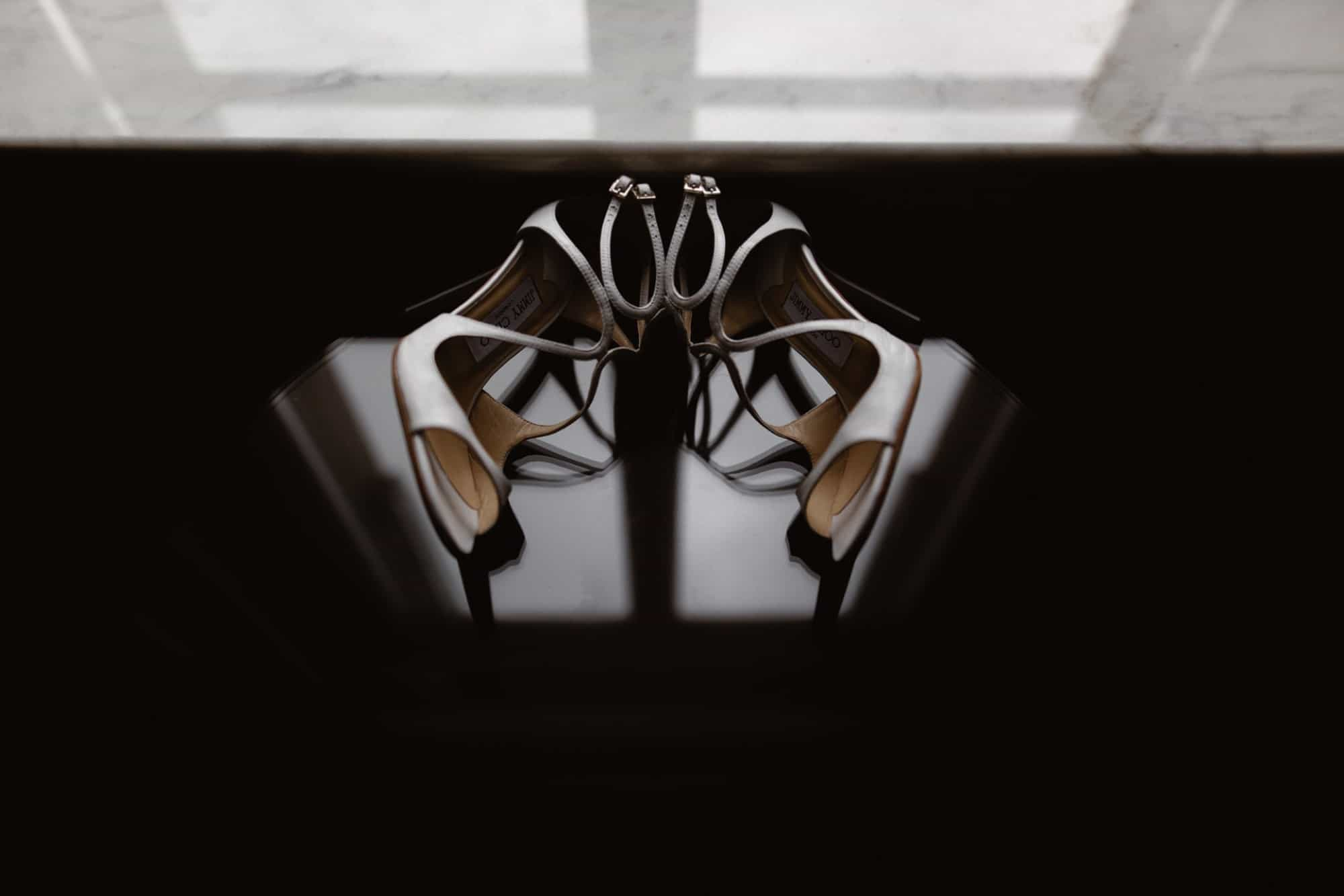 Pair of Jimmy Choo Wedding Shoes on reflective table