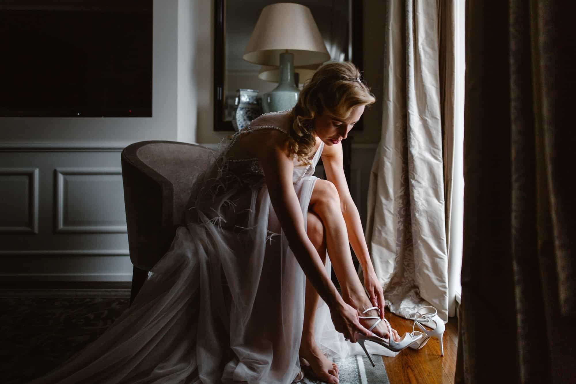 Bride sat putting her wedding shoes on