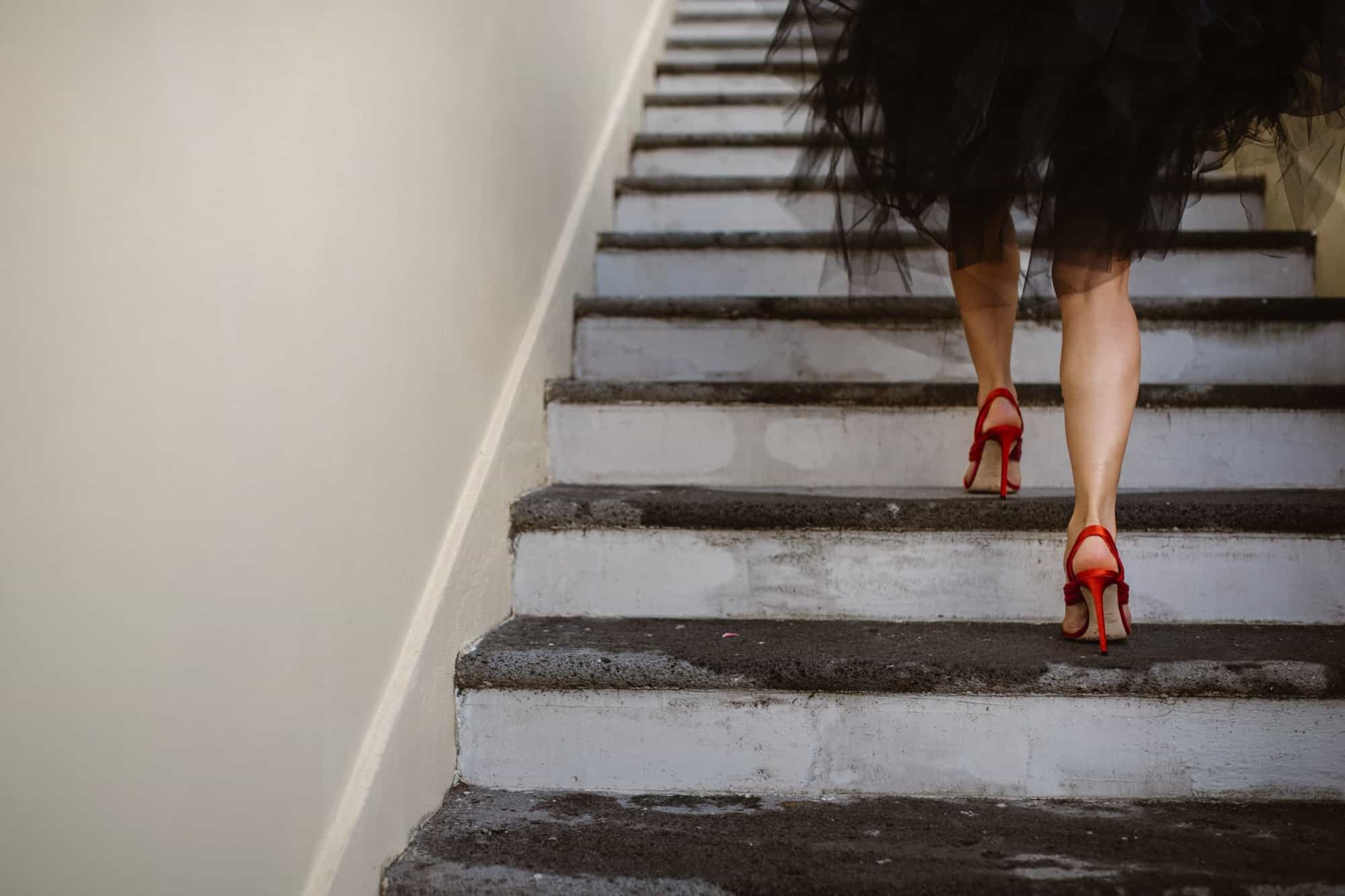 Bride in red wedding shoes walking up stairs