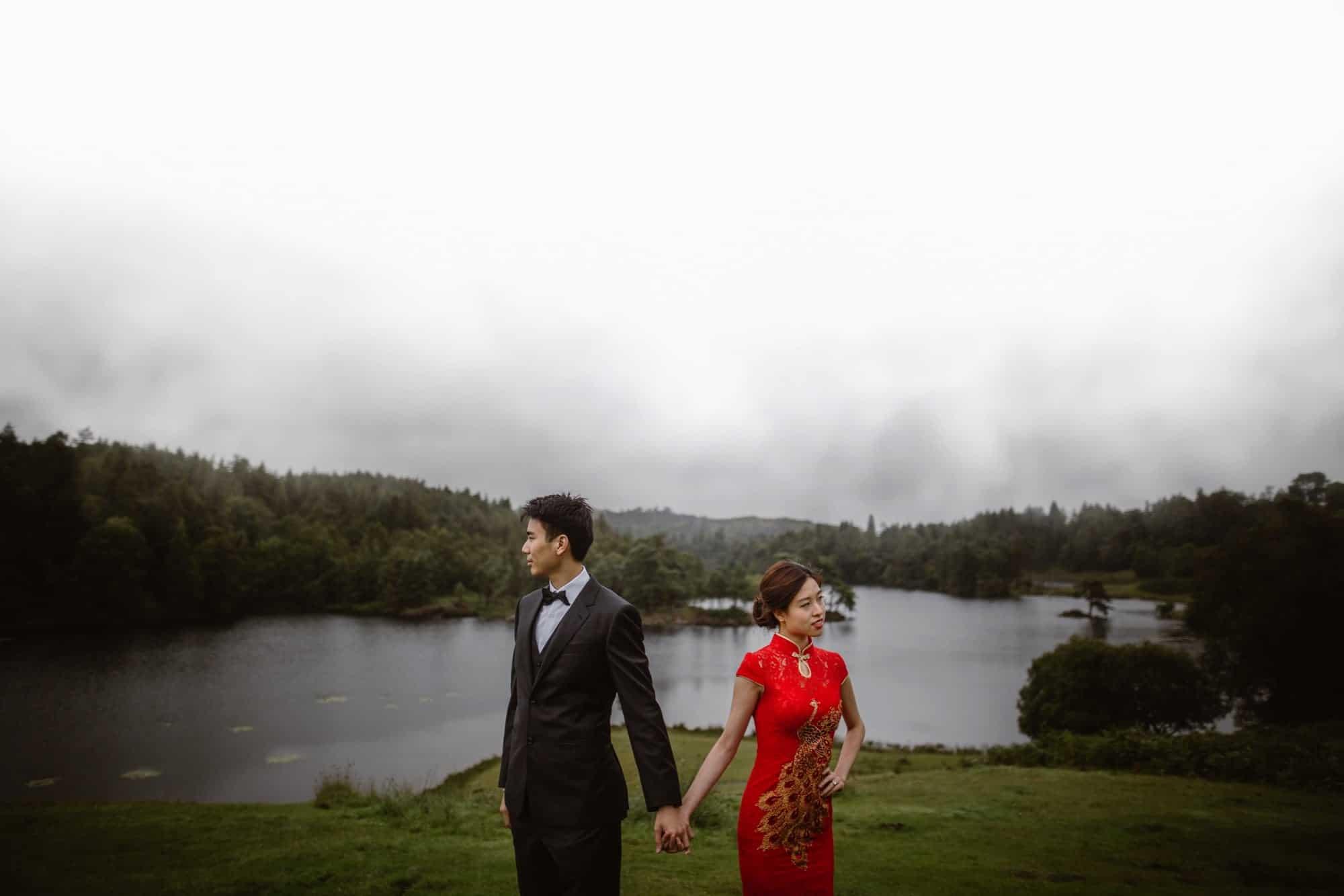 Hong Kong couple hold hands and look at the views at Tarn Hows