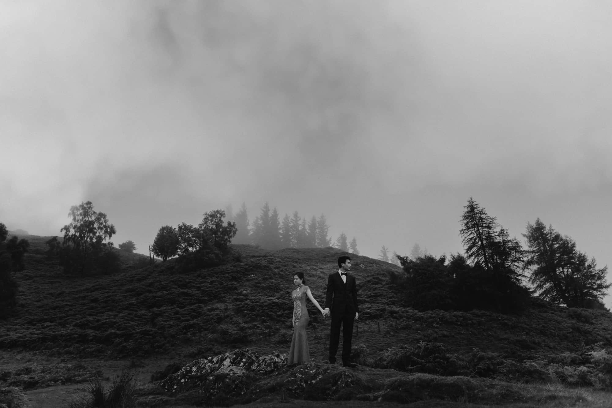 Black & White image of Hong Kong couple in the distance on a hill in Tarn Hows