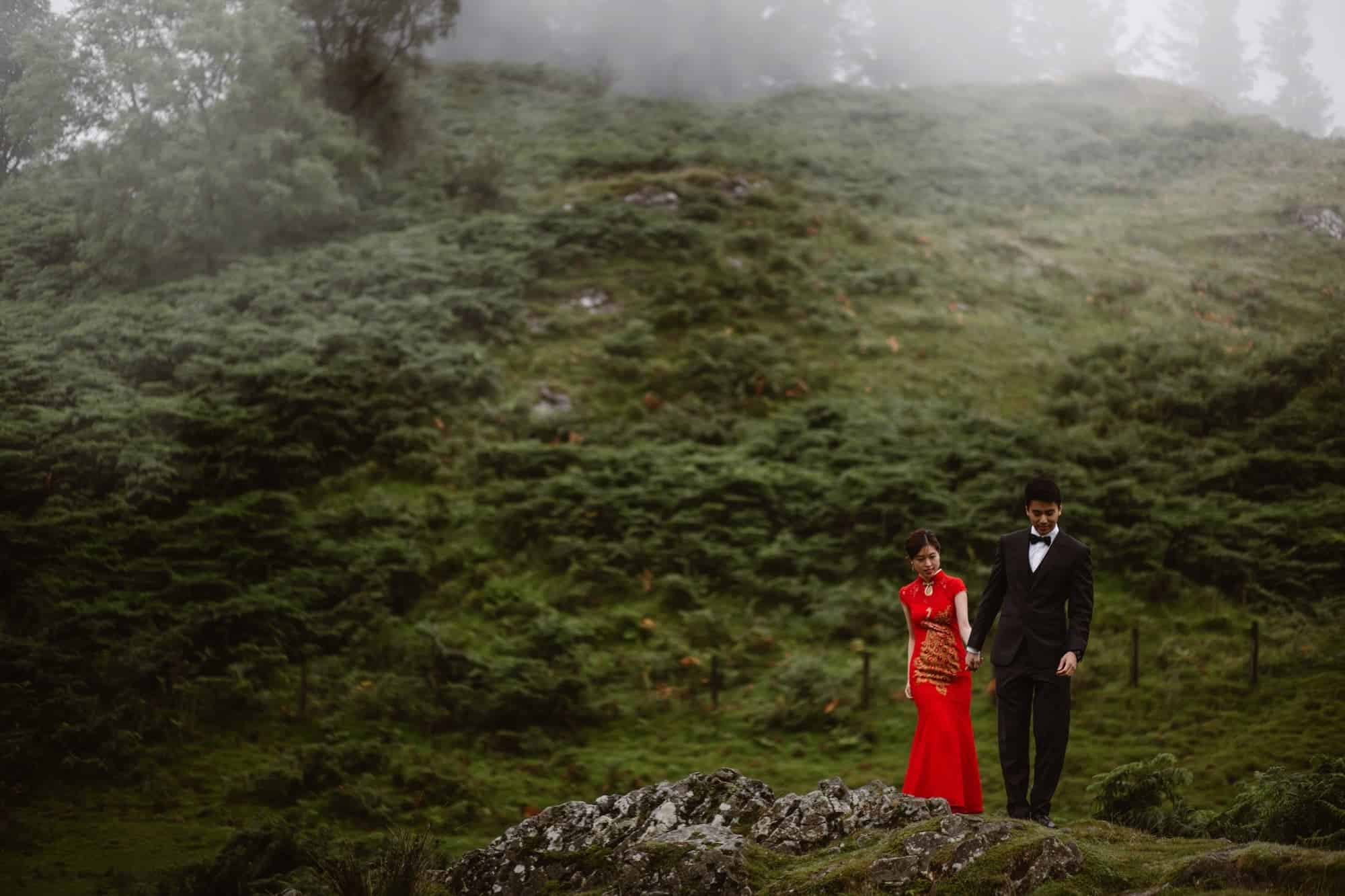 Hong Kong couple walking down a hill in the Lake District holding hands