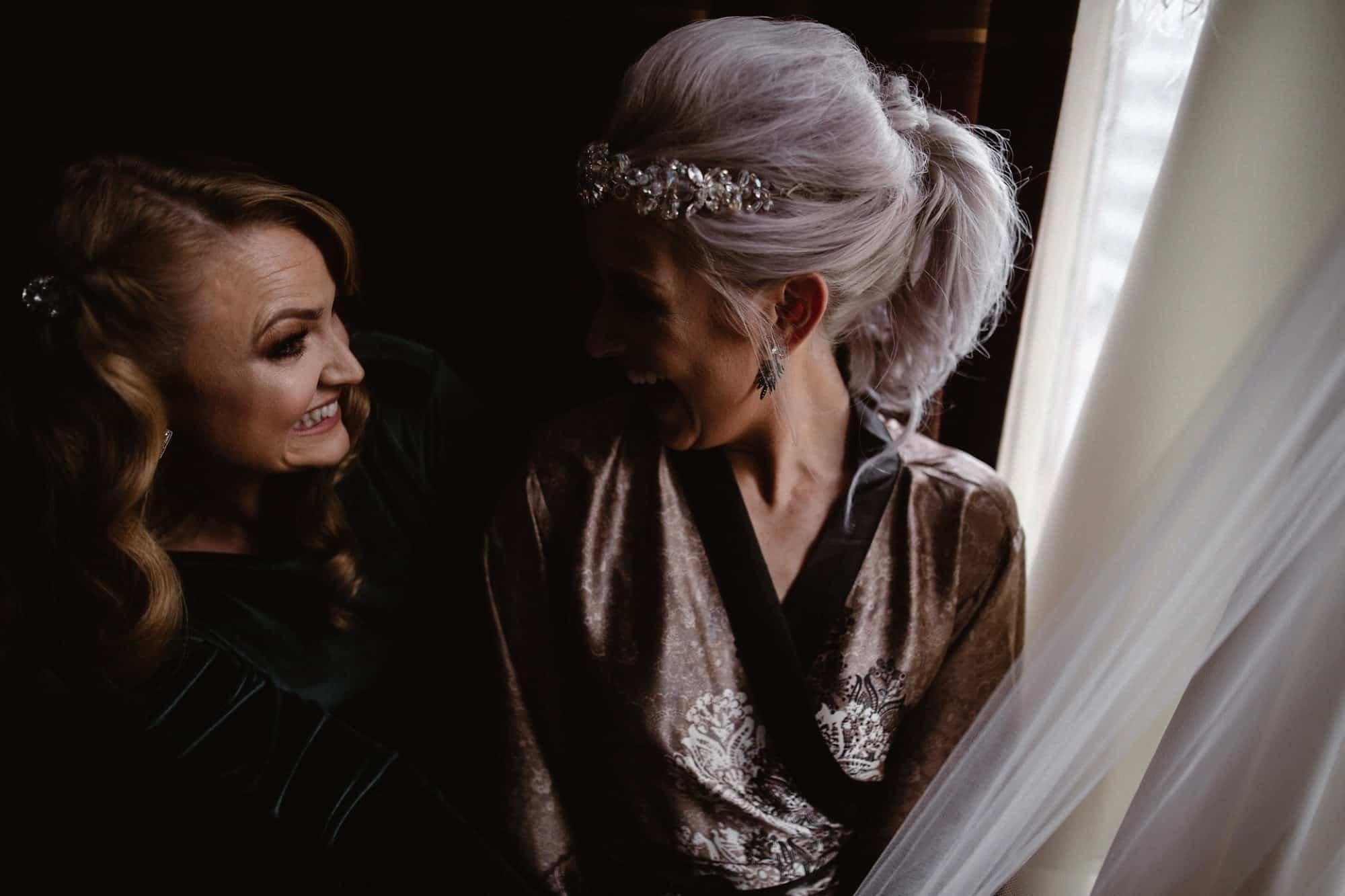 Bride and bridesmaid looking at the wedding dress