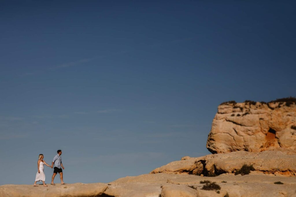 Couple walk hand in hand on the cliff tops of Algar Seco in Faro, Portugal