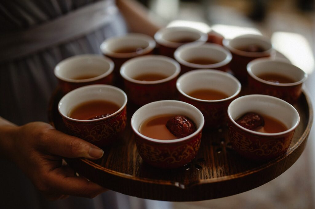 Cups with tea, lotus seeds and red dates on a tray as part of the Ging Chaa or Tea Ceremony
