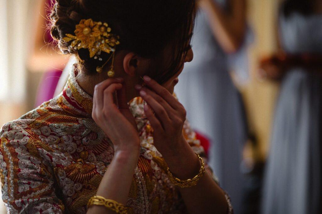 Hong Kong Bride putting gift of pearl earing in her ears