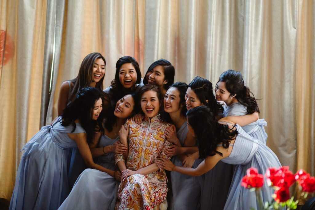 Bride in her Traditional Quipao wedding dress surrounded by her bridesmaids all laughing together.