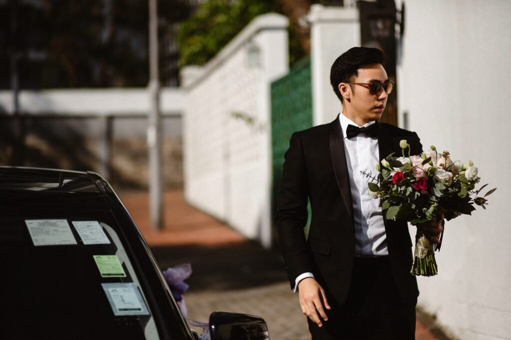 Groomsman holding bouquet of flowers.