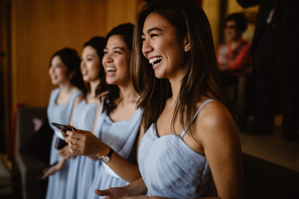Bridesmaids laughing as they watch the traditional Hong Kong Jip San Leung or The Door Games are undertaken by the groom and groomsmen.