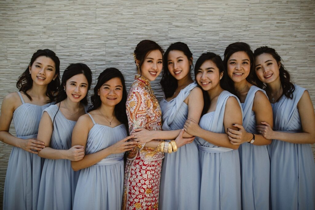 Portrait of Bride in her Traditional Quipao wedding dress with her bridesmaids wearing light lilac dresses