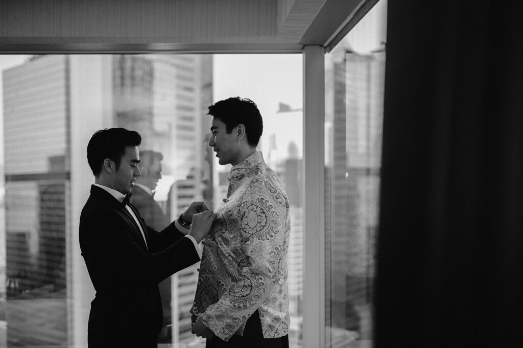 Groomsman helping Groom into traditional Hong Kong wedding outfit