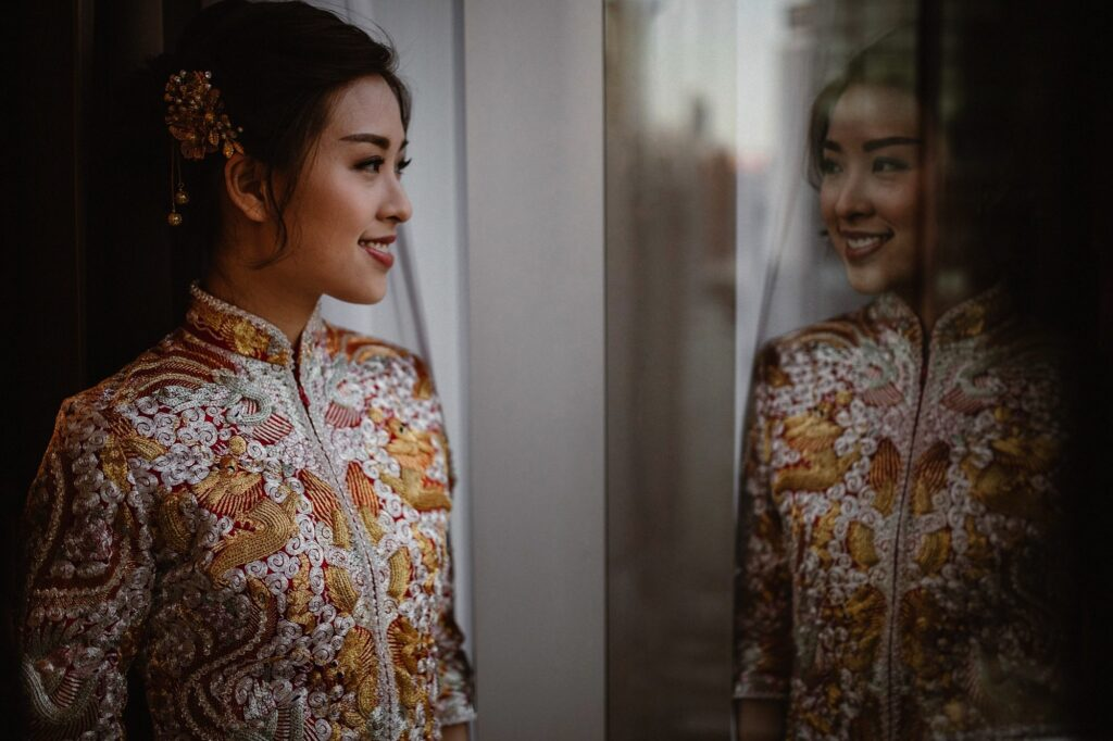Hong Kong Bride wearing traditional chinese wedding dress called a Quipao reflected in window.