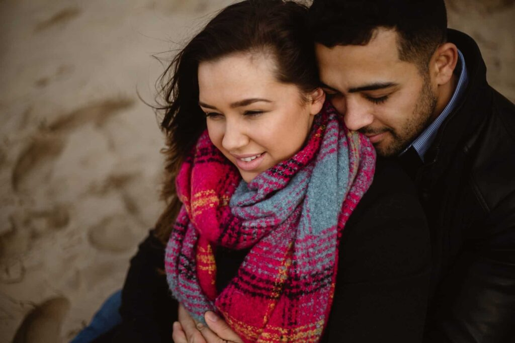 Couple sat on Fomby Beach during their enagement session