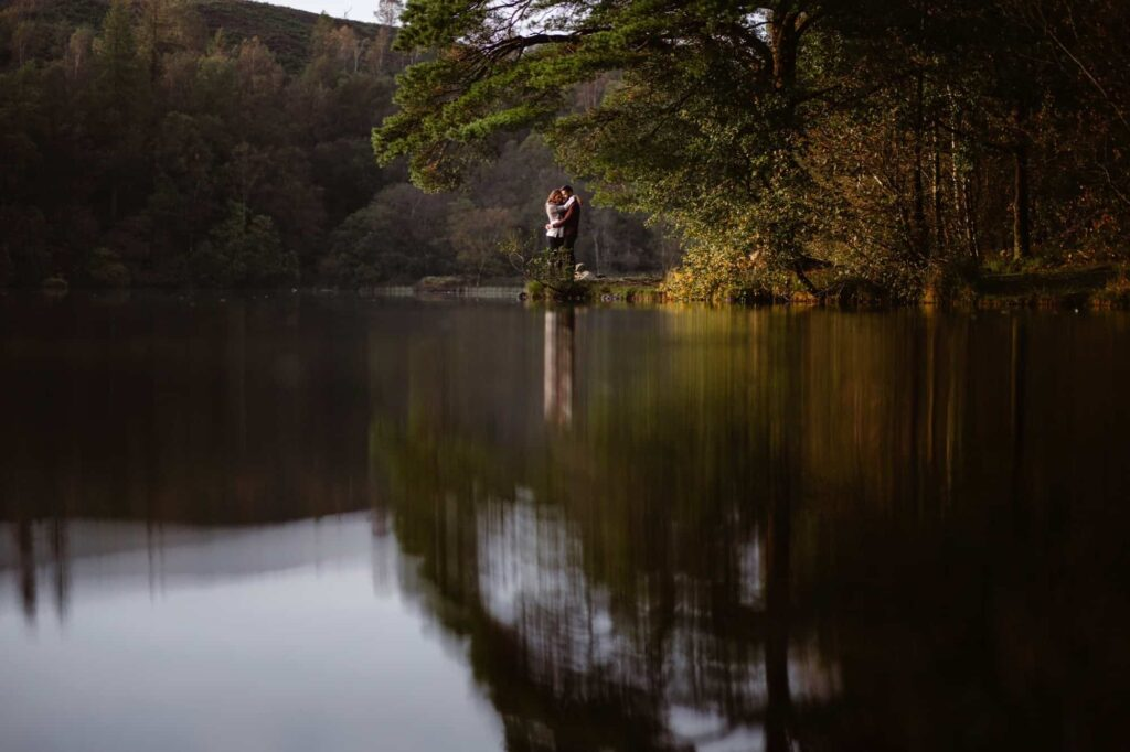 Engaged couple embracing under a tree on edge of a of Lake at High Dam Tarn in The Lake District
