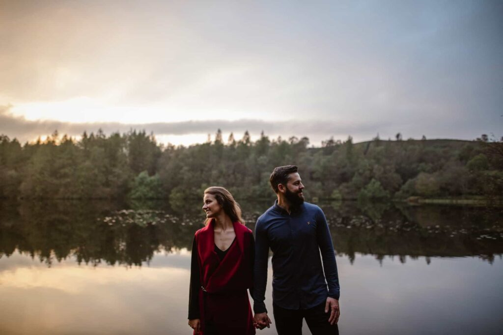 Engaged couple holding hands in front of Lake at High Dam Tarn in The Lake District