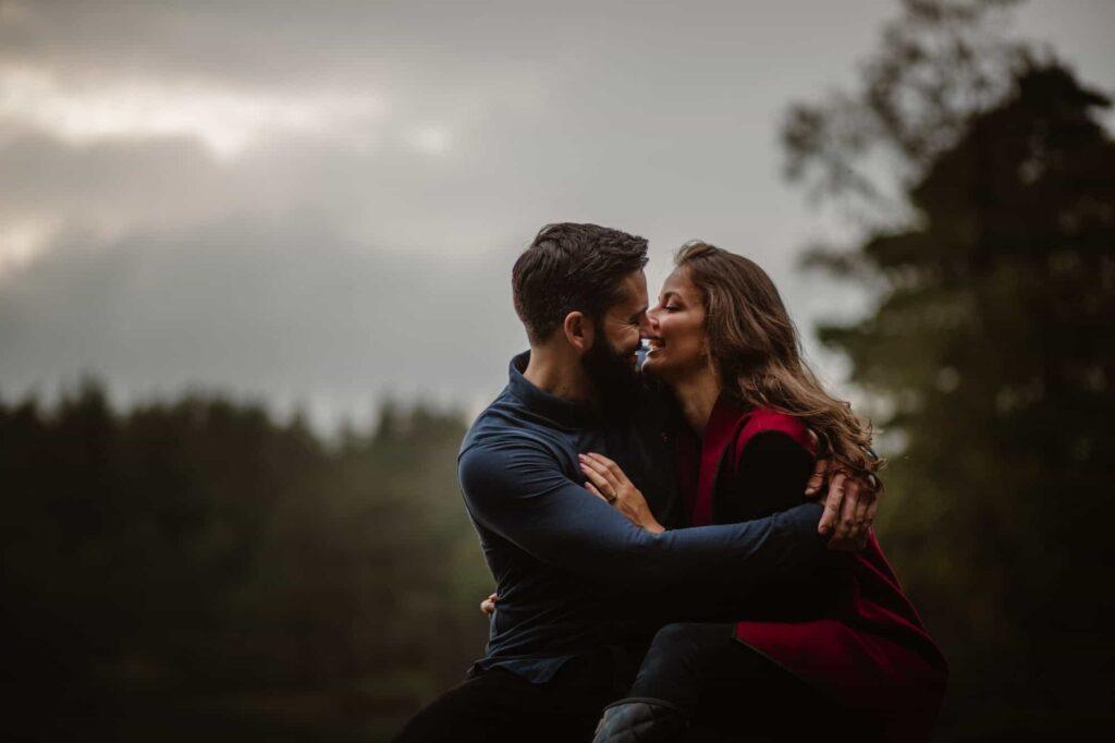 Man hugging woman wearing red coat as she laughs