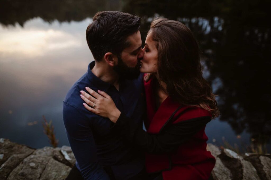 Woman in Red coat kissing fiance by Lake