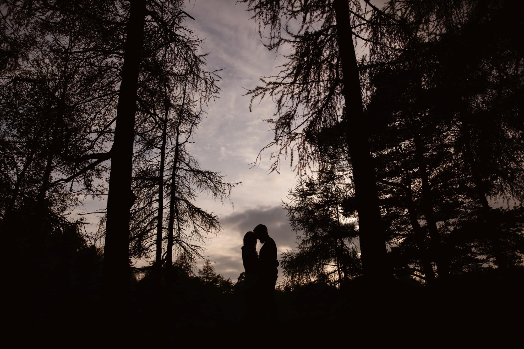 Silouette of Engaged Couple embracing at High Dam Tarn in The Lake District at Sunset