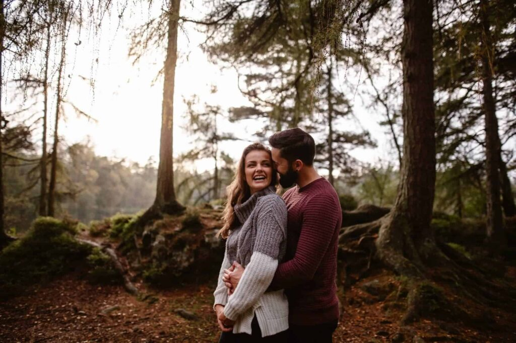Engaged Couple embracing and laughing in woodland at High Dam Tarn in The Lake District